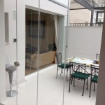 Frameless glass partition doors to sunroom