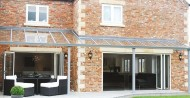 aluminium+glass fixed awning + bifolding doors